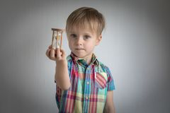 Little boy with a sand clock in his hand.  royalty free stock photography