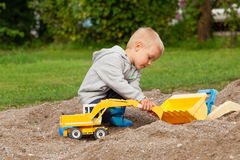 Little boy in the sandbox. Little boy playing with children excavator in the sandbox Stock Images