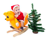 Little boy in Santa Claus suit riding a toy cat Royalty Free Stock Images