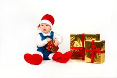 Little boy in Santa hat with a bunch of gifts Stock Photos