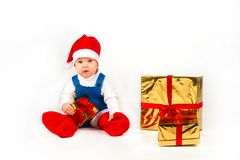Little boy in Santa hat with a bunch of gifts Royalty Free Stock Photos