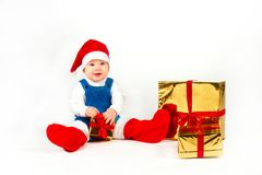 Little boy in Santa hat with a bunch of gifts Stock Photo