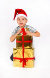 Little boy in Santa hat with a bunch of gifts Royalty Free Stock Images