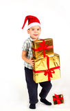Little boy in Santa hat with a bunch of gifts Stock Image