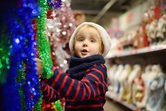 Little boy in Santa hat chooses Christmas decorations at market. Traditional Xmas decoration royalty free stock images