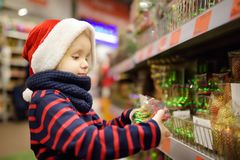Little boy in Santa hat chooses Christmas decorations at market. Traditional Xmas decoration stock photos