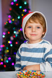 Little boy in santa hat with christmas tree and lights Stock Photos