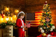 Little boy santa hat and costume having fun. American traditions concept. Toddler celebrate christmas. True american. Small child cheerful mood waving flag. Kid stock photography