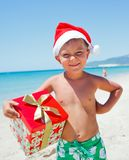 Little boy in santa hat. Cute little boy in Santa hat with gift on tropical vacation Stock Photos
