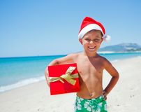 Little boy in santa hat. Cute little boy in Santa hat with gift on tropical vacation Royalty Free Stock Photos