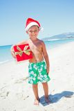 Little boy in santa hat. Cute little boy in Santa hat with gift on tropical vacation Stock Image