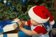 Little boy in santa hat holding a gift. Cute little boy in santa hat holding a gift near Christmas tree. child with present. xmas kid Royalty Free Stock Image