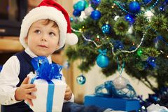 Little boy in santa hat holding a gift. Cute little boy in santa hat holding a gift near Christmas tree. child with present. xmas kid Stock Image