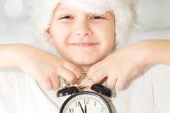 Little boy in santa hat keeps alarm clock, focus on a clock. Stock Photos