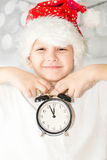 Little boy in santa hat keeps alarm clock, focus on a clock. Stock Photography