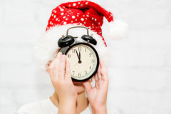 Little boy in santa hat keeps alarm clock, focus on a clock. Royalty Free Stock Photography