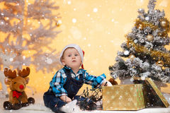 Little boy in a santa hat near Christmas tree enjoys gift and toy. S Stock Photo