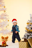 Little boy in a santa hat near Christmas tree enjoys gift and toy. S Royalty Free Stock Photography