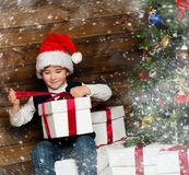 Little boy in Santa hat opening gift box Royalty Free Stock Photography