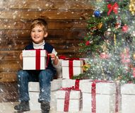 Little boy in Santa hat opening gift box Royalty Free Stock Photo