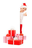 Little boy in Santa hat peeking from behind blank. Sign billboard and showing thumbs up. Isolated on white background. Space for Your Text. Sale, holidays royalty free stock photography