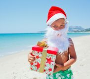 Little boy in santa hat. Portrait of cute little boy in Santa hat with gift on tropical vacation Stock Photography