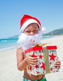 Little boy in santa hat. Portrait of cute little boy in Santa hat with gift on tropical vacation Stock Image