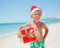 Little boy in santa hat. Portrait of cute little boy in Santa hat with gift on tropical vacation Royalty Free Stock Photography