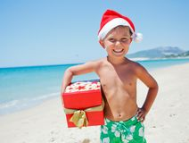 Little boy in santa hat. Portrait of cute little boy in Santa hat with gift on tropical vacation Royalty Free Stock Images
