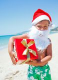Little boy in santa hat. Portrait of cute little boy in Santa hat with gift on tropical vacation Royalty Free Stock Photos