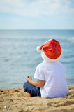 Little boy in Santa hat sitting on sand ocean Stock Image