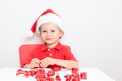 Little boy in Santa hat sorting Christmas gifts Royalty Free Stock Photos