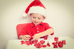 Little boy in Santa hat sorting Christmas gifts Stock Photo