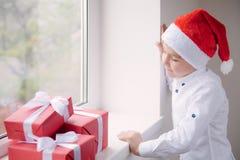 Little boy in Santa hat standing by window looking at the gifts. Little boy in Santa hat standing at the window looking at the gifts Stock Photo