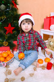 Little boy in Santa hat with tangerine sits near Christmas tree Royalty Free Stock Photo