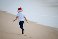 Little boy in Santa hat walking away on seashore. Picture of  joyful little kid in Santa hat walking away on seashore barefoot. Backview of kid in front of swash Royalty Free Stock Photos