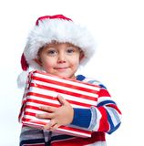 Little boy in Santa's hat with gift box Stock Photos