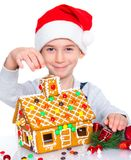 Little boy in Santa's hat with gingerbread house Stock Image