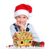 Little boy in Santa's hat with gingerbread house Stock Photos