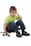 Little boy sat on skateboard Royalty Free Stock Photography