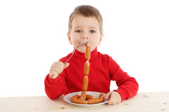Little boy with sausages on fork Stock Photography