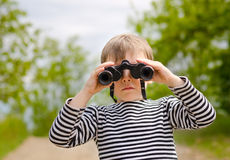 Little boy scanning the woods with binoculars Stock Photo