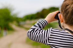 Little boy scanning the woods with binoculars Stock Image