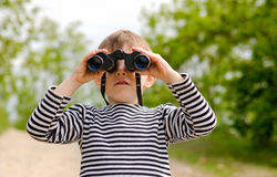 Little boy scanning the woods with binoculars Stock Photos