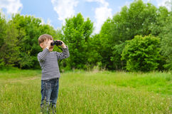 Little boy scanning the woods with binoculars. Little boy standing in a green grassy field scanning the surrounding woods with binoculars as he explores the Royalty Free Stock Photos
