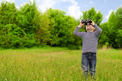 Little boy scanning the woods with binoculars. Little boy standing in a green grassy field scanning the surrounding woods with binoculars as he explores the Stock Photography