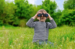 Little boy scanning the woods with binoculars Stock Photography