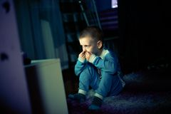 Little boy is scared by television Royalty Free Stock Image