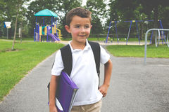 Little boy with school backpack and book in the play yard lookin Stock Photos