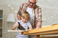 Little Boy sciant le conseil en bois photographie stock libre de droits